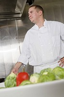 Male chef with vegetables in foreground