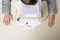Businessman resting head on stack of paperwork (thumbnail)
