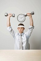 Businessman lifting weights (thumbnail)