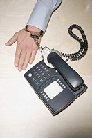 Businessman handcuffed to telephone