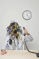 Businessman with tangle of computer wires on head