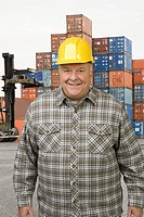 Male dock worker in front of cargo containers