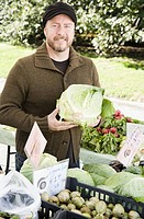 Man holding lettuce at vegetable stand