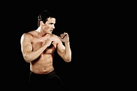 Bare-chested man in boxing stance