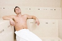 Young man sitting in sauna