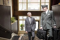 Businessman and bellhop walking up stairs