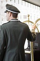 Bellhop with hand on luggage cart