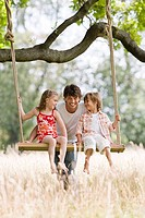 Children on swing with father