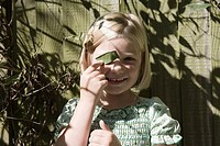 Woman covering her eye with a leaf