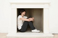 Young man sitting in a fireplace