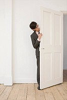 Businessman hiding behind a door