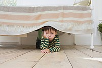 Boy hiding under a bed