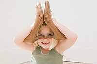 Girl playing with a pair of heeled shoes