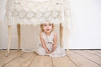 Girl hiding under a table