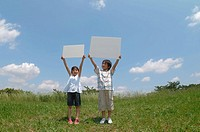 Two Children Holding Signs