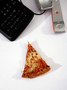 Slice of pizza next to phone on office desk
