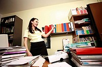 Female office worker in cluttered office