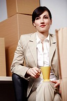 Businesswoman with coffee cup among boxes (thumbnail)