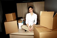 Businesswoman on desk among boxes