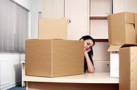 Businesswoman among boxes at desk