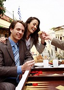 Business couple at taverna with backgammon, appetizers, and ouzo