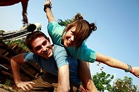 Teenage couple playing on piggy back in amusement park