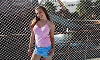 Female teenager posing at fence