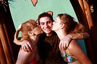 Two female teenagers kissing male teenager on cheek