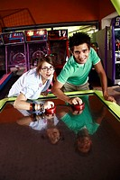 Teenage couple playing game in arcade (thumbnail)