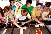 Teenagers playing game in amusement park (thumbnail)