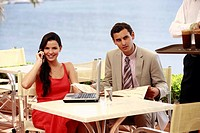 Couple at seaside cafe table with laptop