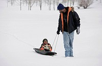 Father pulling son on sled