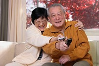 Senior Asian couple having some silly fun to watch their favorite program on tv using the remotes