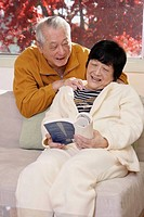 Senior Asian man giving his wife a massage while she reads