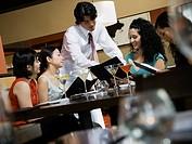 Asian male server explaining menu