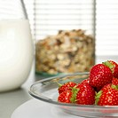 Strawberries on plate, cereals and milk in background