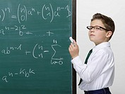 Boy 10-11 standing in front of blackboard, portrait