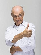 Senior man giving thumbs up, portrait, close-up