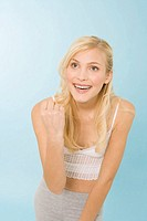 Blonde woman raising fist, smiling, portrait