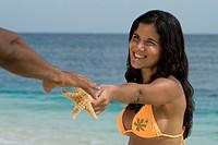 Hispanic woman handing starfish to boyfriend