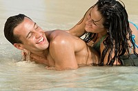 Hispanic couple playing in water
