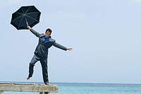 Hispanic businessman holding umbrella on dock