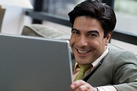 Hispanic businessman holding laptop
