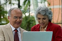 Senior Hispanic couple looking at laptop
