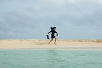 Hispanic businesswoman walking on beach