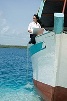 Hispanic businesswoman working on boat