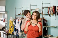 Hispanic man putting necklace on wife