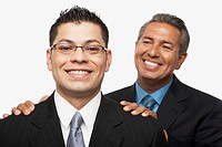 Hispanic businessman smiling at younger businessman