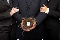Hispanic businesspeople holding nest with dollar sign egg