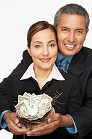 Hispanic professional couple holding nest of money